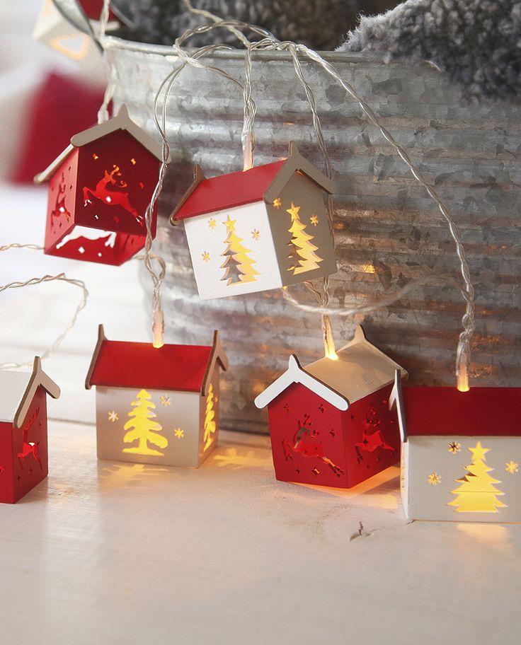 Veldig søt og sjarmerende LED lysslynge fra Star Trading med 10 hvite og røde små hus i treverk med dekor av utskjærte grantrær og reinsdyr. Slyngen kan stilles inn med timer slik at den står 6 timer på og 18 timer av, og den har en brenntid på ca 100 timer per batteribytte.