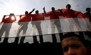 Anti-government protesters hold an Egyptian flag during a mass demonstration in Tahrir Square in Cairo, in February 2011.