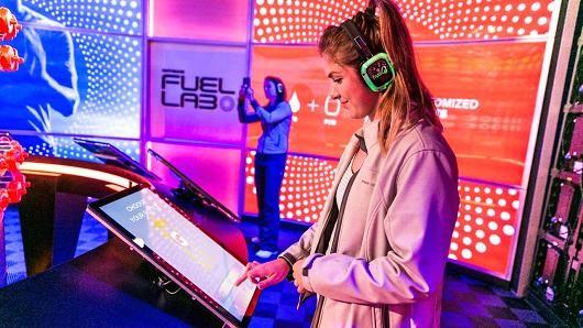 A woman makes her own custom Gatorade inside the Gatorade Fuel Lab at SXSW in Austin, Texas.