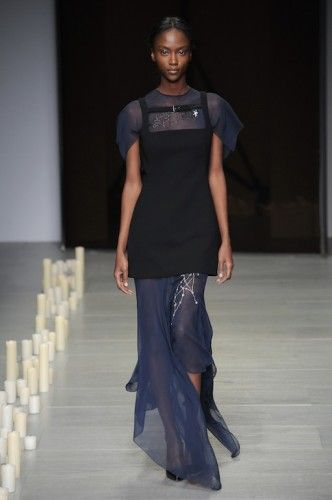 "O glamorous Marios Schwab επέλεξε αυτή τη φορά να δείξει ρούχα που μπορούν να φορεθούν κι εκτός κόκκινου χαλιού. Ενώ παρέλασαν εντυπωσιακά maxi dresses με διαφάνειες αλλά και ασύμμετρα mini που κατέληγαν σε μια μακριά εσάρπα-ουρά, περισσότερη εντύπωση προκάλεσαν τα καθημερινά του looks. Μαύρα φορέματα συνδυασμένα με bomber jackets, δερμάτινα παντελόνια και φούστες ταιριασμένα με «ευρύχωρα» ζιβάγκο και ""καθώς πρέπει"" πουκάμισα έδωσαν το στίγμα της φετινής κολεξιόν του Ελληνοαυστριακού…"