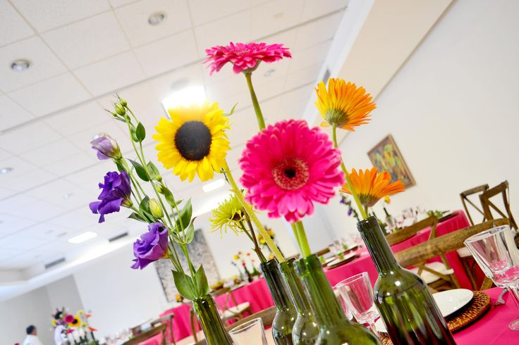 Decoración de Happy Hour en salones del museo de arte, con estilo innovador con botellas de vino, troncos de madera dando un efecto diferente. Con girasoles, dragones, gerberas, lisanthium, Fuji verde, green balls