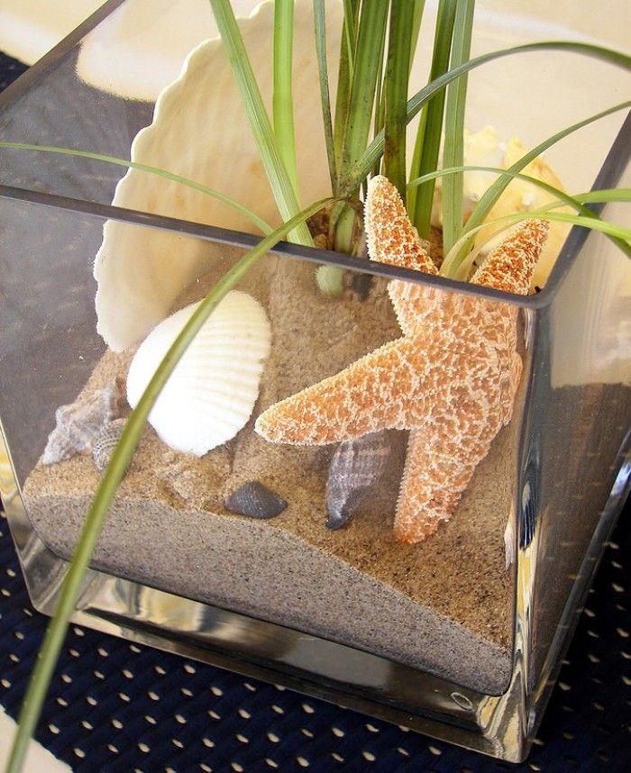 Accubak gevuld met zand en een enig sprietenplantje. Aanvullen met schelpen en je haalt het strand in huis. Ook leuk met een kaars!