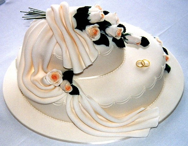 Ivory oval stacked cakes, draped icing and hand moulded sugar roses and leaves.