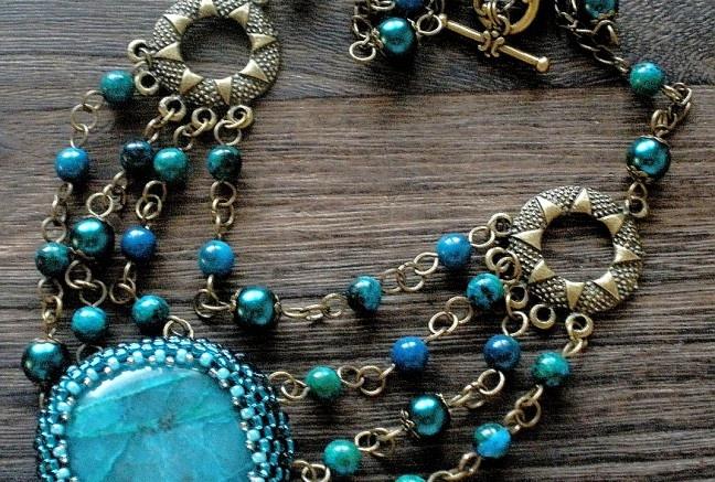 Výrazný s antickým nádychom -kabošon chryzocolly je obšitý do výrazného japonského rokajlu so trieborným prieťahom (dodáva úžasný žiarivý efekt) -doplnený je voskovanými perlami, guľkami azuromalachitu a masívnymi antickými medzikusmy v tvare slnka  Náušničky pozostávajú z rovnakého materiálu