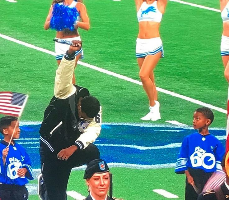 Detroit artist Rico Lavelle takes a knee with a raised fist after singing the national anthem at Ford Field, before the Lions -  Falcons game, September the 24, 2017.
