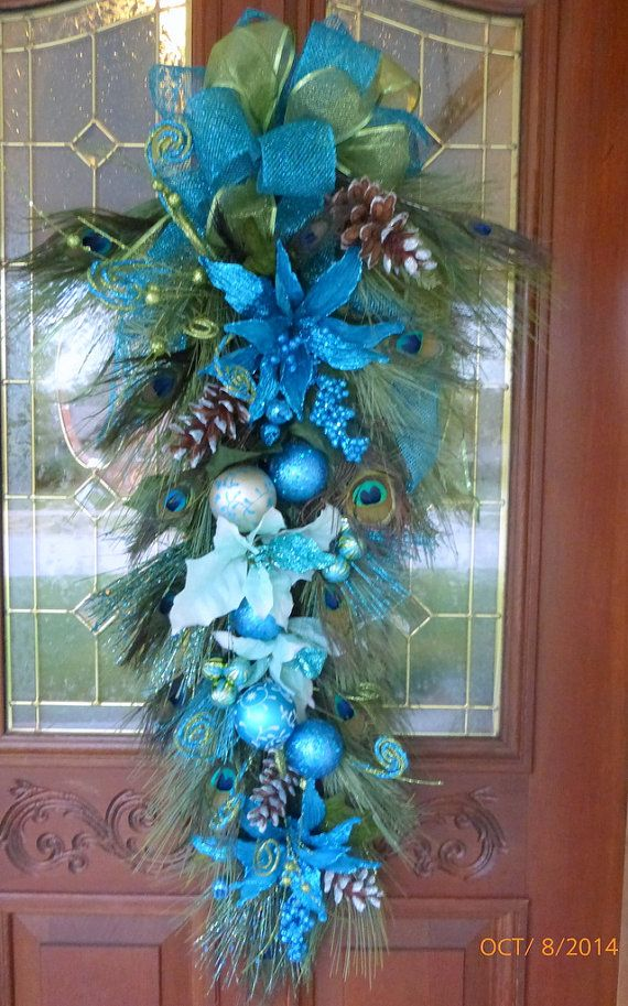 Beautiful Christmas Peacock door swag, extra long at 41.. This is a beautiful Turquoise blue Peacock glittered door swag. It starts off with