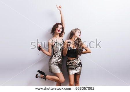 Two charming young women drinking wine and having fun, dancing, enjoying party, hand up. Fashionable skinny girls in sexy shiny dresses with paillettes, pretty wavy hairstyle. Isolated.