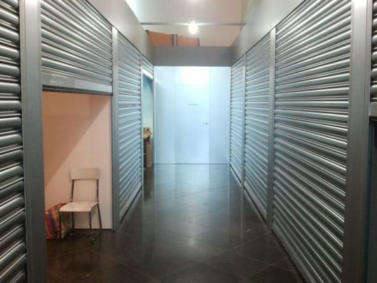 Fiona Tan, Options & Futures Rabo Kunstzone, Utrecht > 'De ruimte is deels veranderd in een serie 'storage rooms', als van een commerciële opslag. Stalen garagedeur na garagedeur vraagt om aandacht, en laat je gaandeweg voelen als een indringer, een voyeur, die hier en daar werkelijk moet gluren door sleuven om kennis van het getoonde te nemen.'