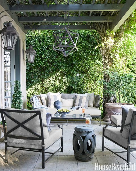 """The house is on a golf course with manicured lawns, so I liked repeating the grays and ivories of the interior against all the greenery,"" designer McDonald says of the limestone-tile veranda in a Los Angeles house, which has Restoration Hardware furniture."
