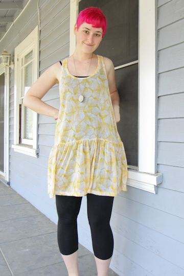 Sheer yellow tunic, black camisole, black capri leggings, stone pendant.: Black Capri