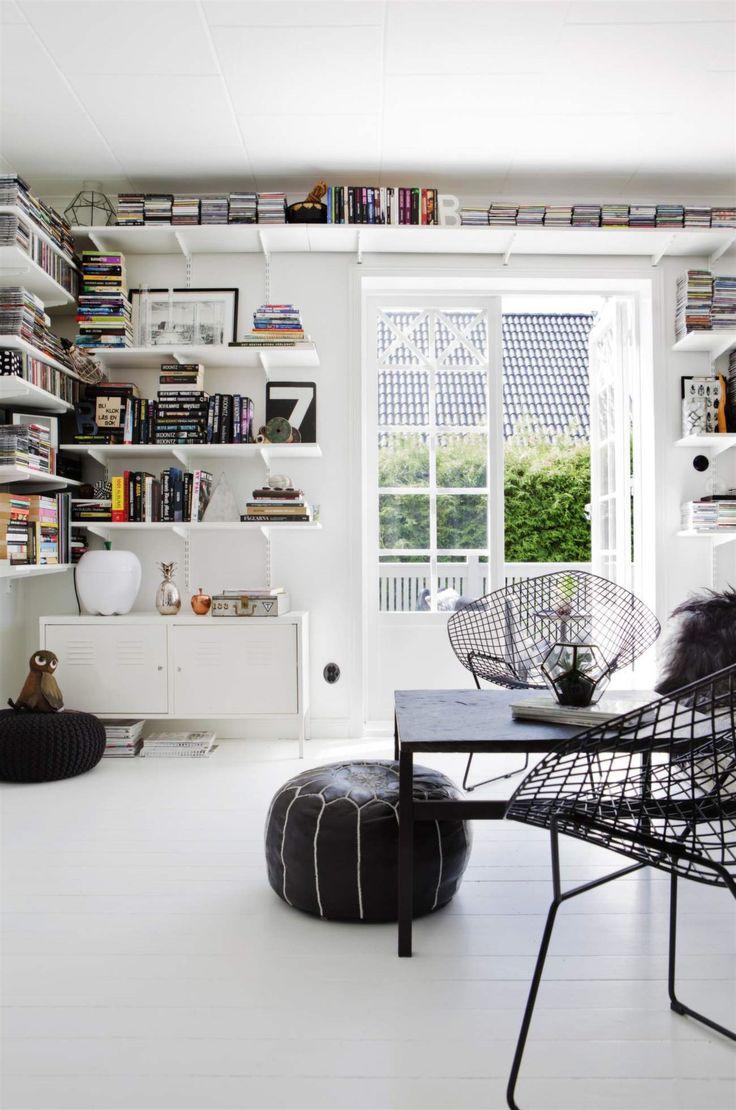 Hyllsystem. Vardagsrumsväggen pryds av ett Elfa-system för böcker och fina inredningsdetaljer.