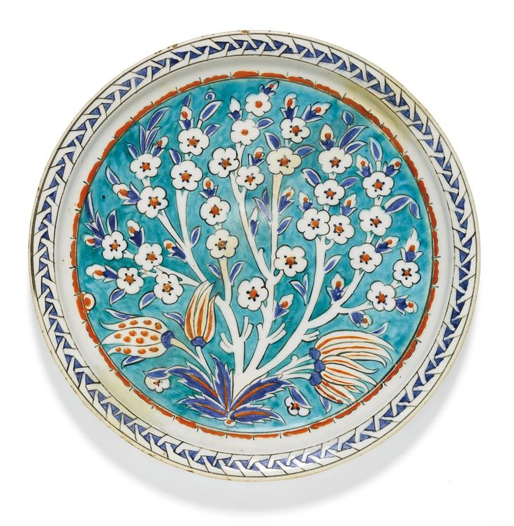 An Iznik polychrome pottery dish with a prunus tree, Turkey, circa 1575-85,    of shallow round form, decorated in underglaze cobalt blue and relief red with a central prunus tree also issuing tulip buds against a turquoise ground, with an abstract border, the exterior with tulip buds and flowerheads, old collection label to underside 29cm. diam.