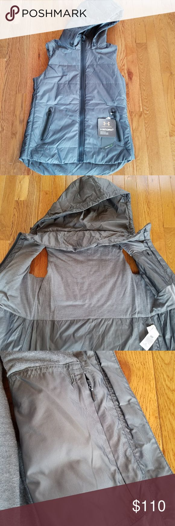 Under Armour Women's Outdoor Vest, Small Under Armour Women's Outdoor Vest, Brand New with tags attached, never been worn. Full zipper with fabric protector at the top; zips to turtleneck style when fully zipped. Size small, loose fit, dark grey. Two zippered hand pockets and one zippered pocket on inside panel. Hood has adjustable bungee cord. Water resistant material to help you stay dry. Primaloft Insulation Eco - warmth without bulk, breathable, superior softness and lightweight comfort,