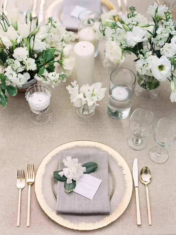 White wedding centerpiece with gold place setting and elegant gold flatware
