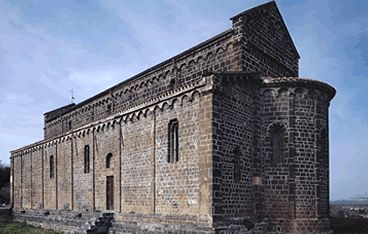 Ardara, chiesa di Santa Maria del Regno - Realizzata in basalto, è una macchia scura che si profila sul pianoro vulcanico su cui sorge l'abitato. Fra le più importanti dell'architettura romanica isolana, colpisce per la grandiosità delle sue forme e per il contrasto, all'interno, del nero basalto con l'oro del polittico cinquecentesco collocato sull'altare. Si tratta di una cappella palatina: costruita vicino al castello di Ardara, questa chiesa rappresentava uno spazio privilegiato dai…