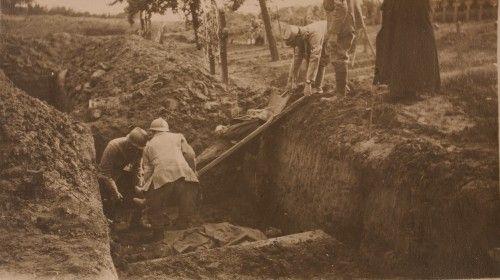 Trois brancardiers français glissent un mort dans une fosse commune. Cimetière militaire de Foucaucourt, 1916.