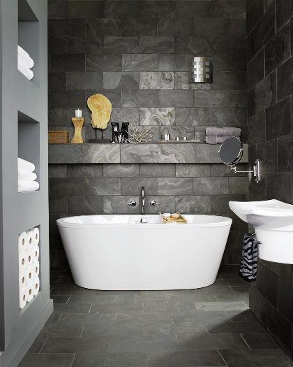 Dark honed slate tiles are used for walls and flooring which contrasts the bright white bathroom facilities.