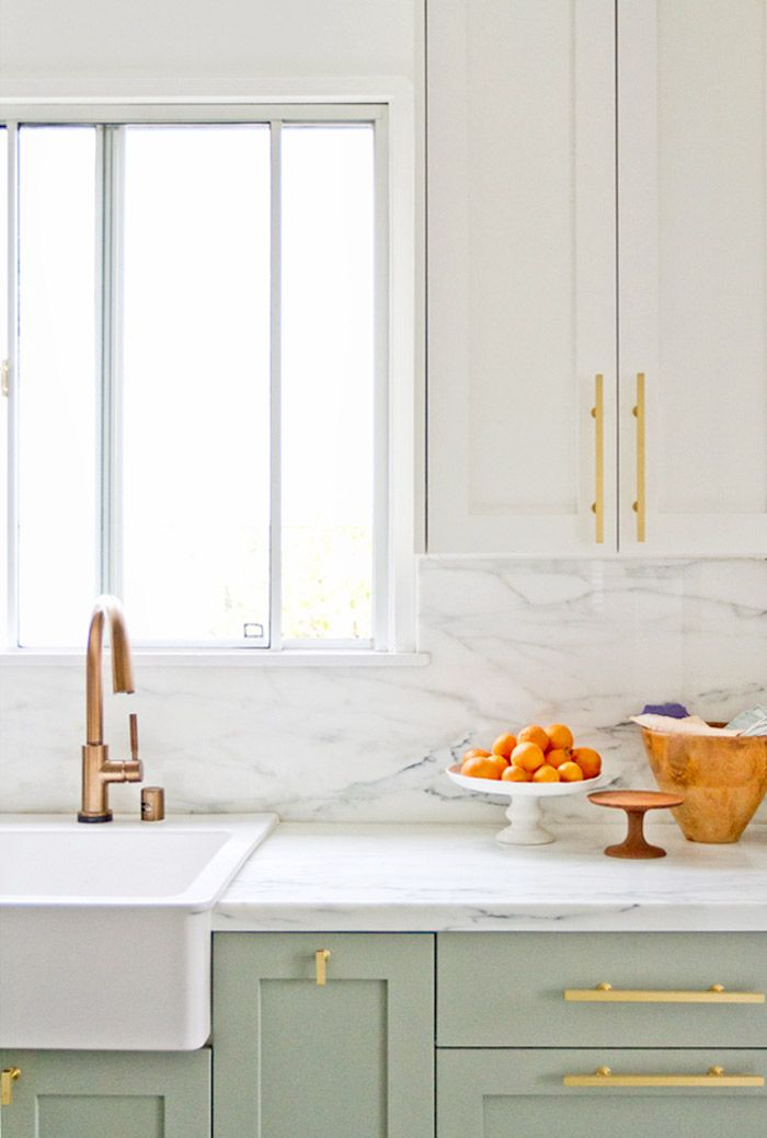 White kitchen with marble backsplash and gold details and accents