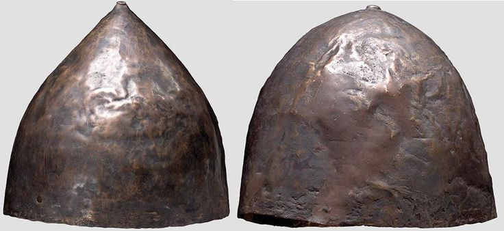 Two Near Eastern helmet,1st half of the 1st millennium B.C.  The skull is of bronze with a large percentage of copper. It is relatively shallow, strongly domed, and comparatively thin-sided. The top of the helmet is crowned with an embossed flat knob. A small hole at the edge of the helmet presumably served for attaching the chin strap, 15.7 cm high, 20,8 cm high Private collection, from Hermann Historica auction