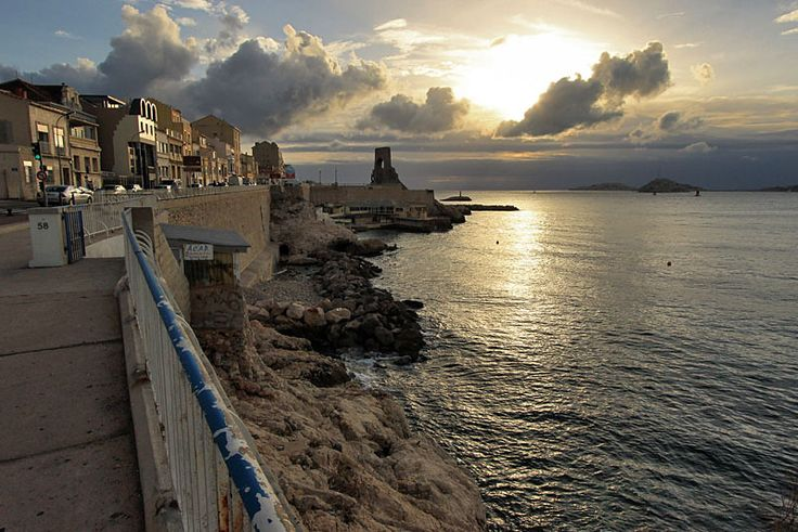 Sunset Lights Up Houses on Corniche Seaside Walk Near Porte de L'Orient Monument in Marseille, France