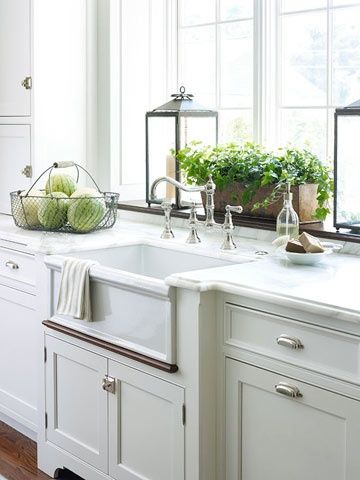Gorgeous cabinetry with latches on the doors, farmhouse sink and an extra deep window ledge over the sink for plants. Absolutely perfect.