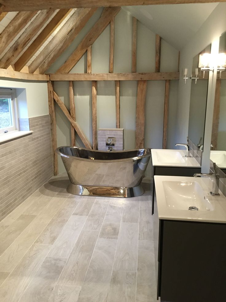 Master ensuite, consisting of free standing polished nickel bath, wall hung duravit vanity units, wall hung Duravitt Starck Me loo. Wood effect porcelain tiles, exposed beams and farrow and ball colours