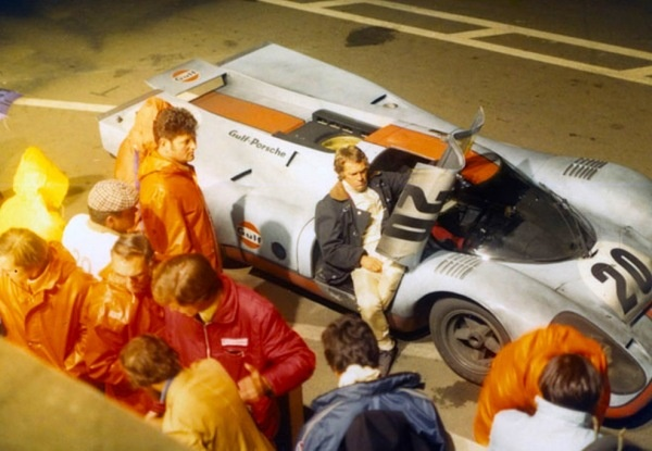 """Steve McQueen and the iconic Gulf Porsche 917K that was entered by McQeen's Solar Productions at the actual 1970 24 Hours of Le Mans for the filming of 1971′s epic racing movie, """"Le Mans."""" The racecar was driven by Jo Siffert and Brian Redman. Vic Elford, driver of the race-leader #25 Porsche 917K called it, """"a monster… the long tail had to be driven like it was on rails""""."""