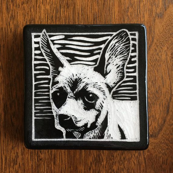 Handmade Tile. Stoneware clay with black slip and clear glaze.  This 4inx4inx.5in tile is a hand-carved portrait of Oxana, an adorable chihuahua mix recently adopted from the Seattle Humane Society. This tile comes with a hook and is ready for hanging. It's the perfect gift for your favorite pet lover. For every shelter dog tile sold, $5 will go to the Seattle Humane Society.