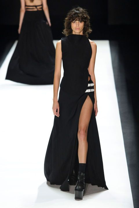 """Long. Lean. Lithe. Vera Wang scribbled and messaged to the masses hours before her fall show. And the start of her collection delivered, with floor-sweeping gowns and separates with up-to-there slits and tunics that were held together with belts, buckles and the merest ties across the models' backs. Insert """"sexy back"""" quips here."""