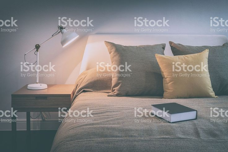 cozy bedroom interior with book and reading lamp royalty-free stock photo