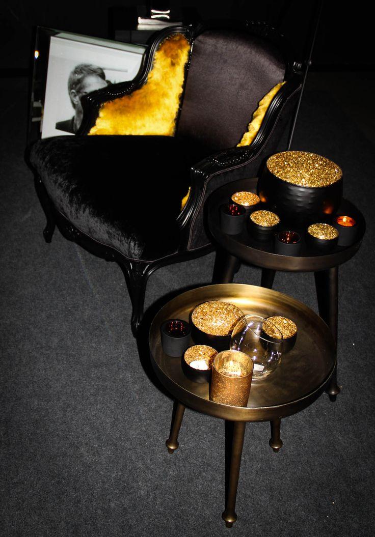 Fauteuil recouvert en noir et ocre avec différentes textures (velours, fausse fourrure, soie) avec petites tables de salons bronzes.