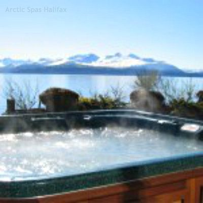 A hot tub with a view of snow covered mountains.