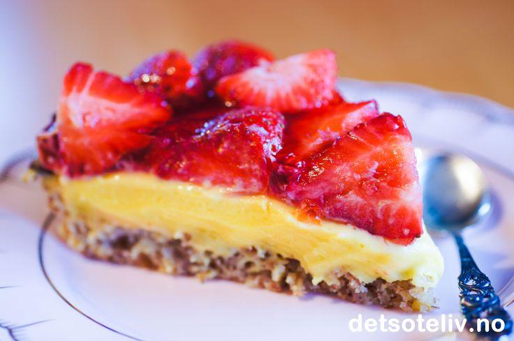 """Her har du en drøm av en kake!! """"Jordbærsuksess"""" er basert på den alltid populære """"Suksesskaken"""", som er en kjempedeilig mandelkake med eggekrem og mandelpynt (du finner oppskriften på detsoteliv.no). Jordbærsuksess er i tillegg dekket med jordbær og jordbærgelé. Litt revet sjokolade langsmed kanten på kaken gir den siste prikken over i'en. Se også oppskrift på Bringebærsuksess og Blåbærsuksess."""