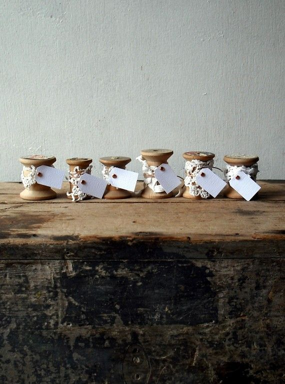 place cards made from vintage wooden spools and adorned with bits of vintage lace