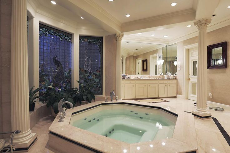 Fabulous master bathroom with marble slab walls, octagonal spa set in stained glass bay window alcove, separate shower, and his and her separate commodes