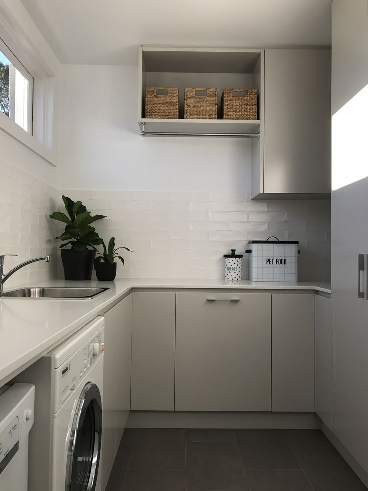 Light filled contemporary laundry.  Stone benchtops, subway tile splashback.  Neutral scheme.  Storage. Lisa Banducci Design
