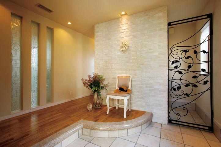 円形上り框(あがちかまち)と石の壁が印象的な玄関ホール。 ロートアイアンの扉の奥はシューズインクローゼットです。|デザイン|ナチュラル|タイル|