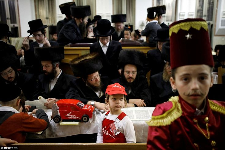 Ultra-Orthodox Jewish men take part in the reading from the Book of Esther ceremony in a s...