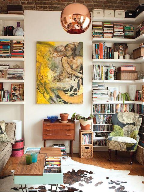 chão de madeira móveis e outras madeiras, poltrona estampada, quadro grande com cor, prateleiras e objetos