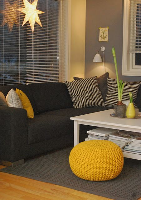 Gray walls and black couch with yellow accent pieces.