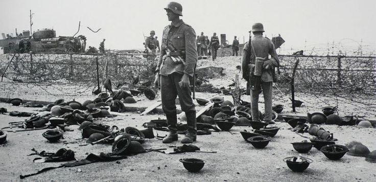 German soldiers stand behind a barbed wire obstacle on the beaches of Dieppe, among dozens of helmets, likely left behind by Allied prisoners after the 19 August 1942 Dieppe Raid.