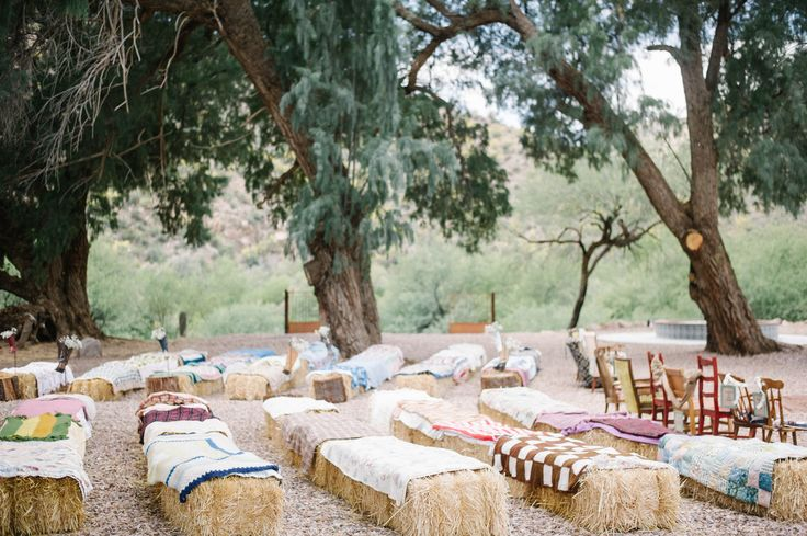 Wedding seating. Hay bails and quilts with vintage chairs