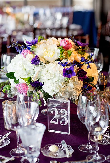 Brides.com: A Traditional Wedding in Chicago, Illinois. Two types of floral centerpieces, each in keeping with the couple's blue and purple color palette, were used throughout the reception space. One centerpiece mixed fluffy white hydrangea and peonies with lush pink and purple buds.