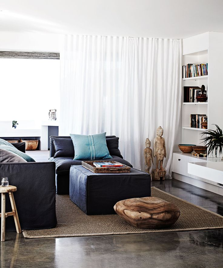 """In the open-plan casual family area, layers of textural interest have been added through accessories, such as linen slip covers on the sofas, a large carved piece of timber on the floor and a sisal rug from the [Natural Floorcovering Centre](http://www.naturalfloor.com.au/