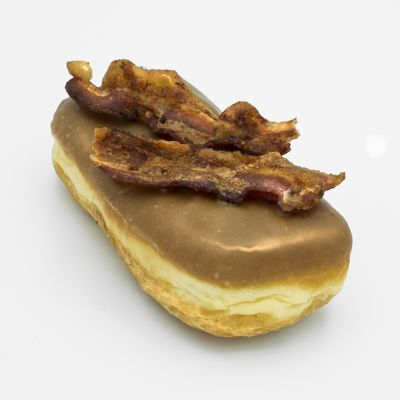Image of a Bacon Maple Bar Doughnut -- a bar shaped raised yeast doughnut dipped in light brown maple icing, and topped with two diagonal slices of bacon; shown from the side and slightly rotated