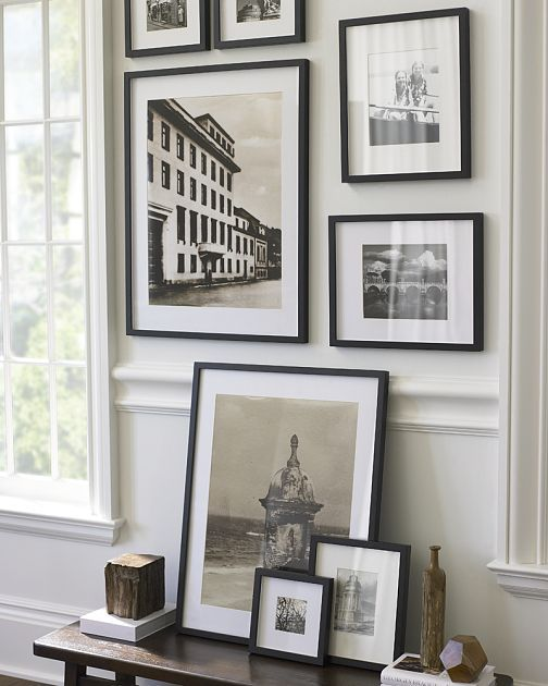 Continue your framed photographs etchings and other black and white images from the wall to table for interest and unity black frames and white mats for a
