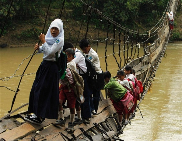 Kids crossing a bridge on their way to school after heavy flooding - Indonesia   (© REUTERS / Beawiharta)