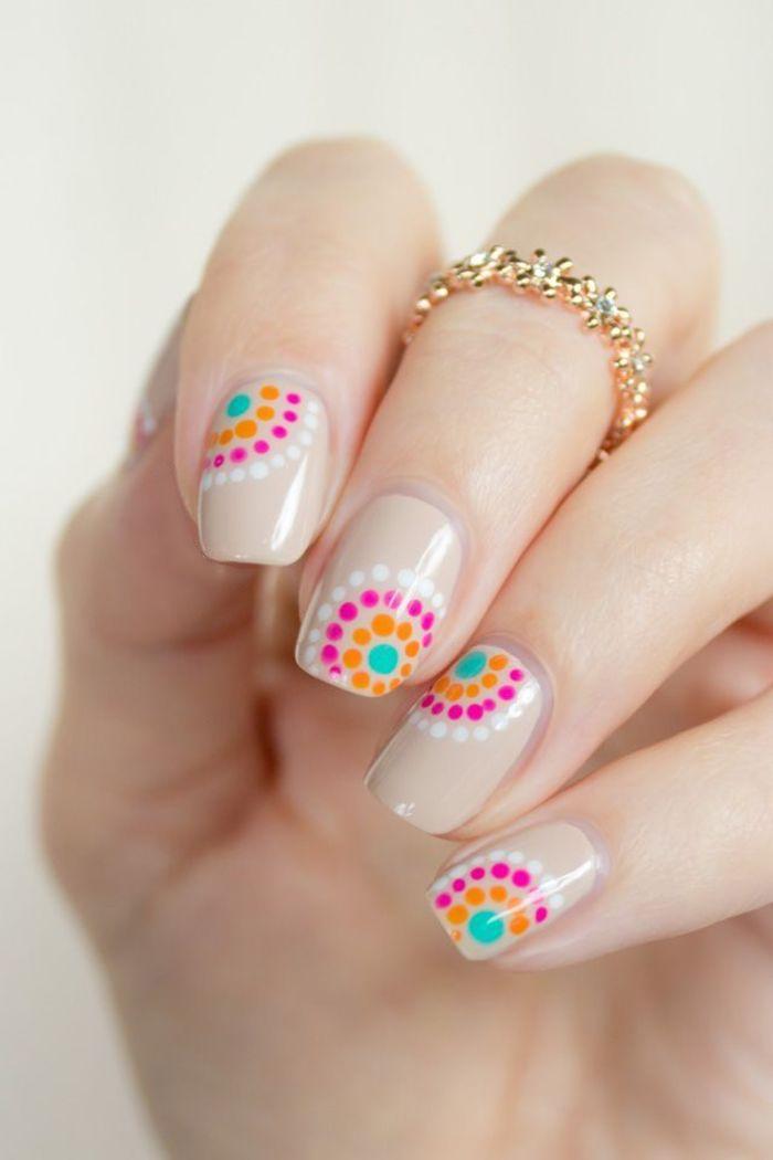 Uñas decoradas en color nude con puntos rosas y naranjas