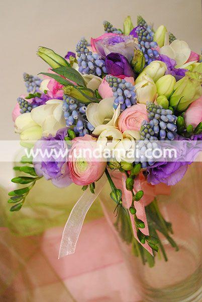 Buchet de mireasa delicat, in degrade, din flori de primavara: muscari, ranunculus roz, frezii mov, lisianthus mov deschis, frezii albe, lisianthus alb-verde, legat cu funda din saten roz