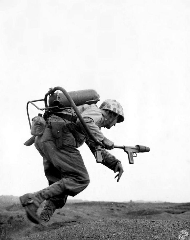 Un Marine américain de la compagnie «E», 9e Régiment de Marines, 3ème Division Marine, porte un lance-flammes avec charges sur une crête à attaquer un pilulier japonais à Motoyama aérodrome occupés pendant la bataille d'Iwo Jima (Détachement de l'opération). Iwo Jima, îles Bonin, Japon. Février 1945. Image prise par David G. Christian, United States Marine Corps.